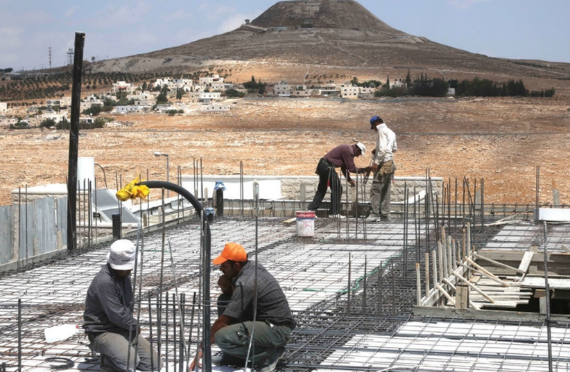 Arab construction workers atop a building in the Tekoa settlement. (photo credit: REUTERS)