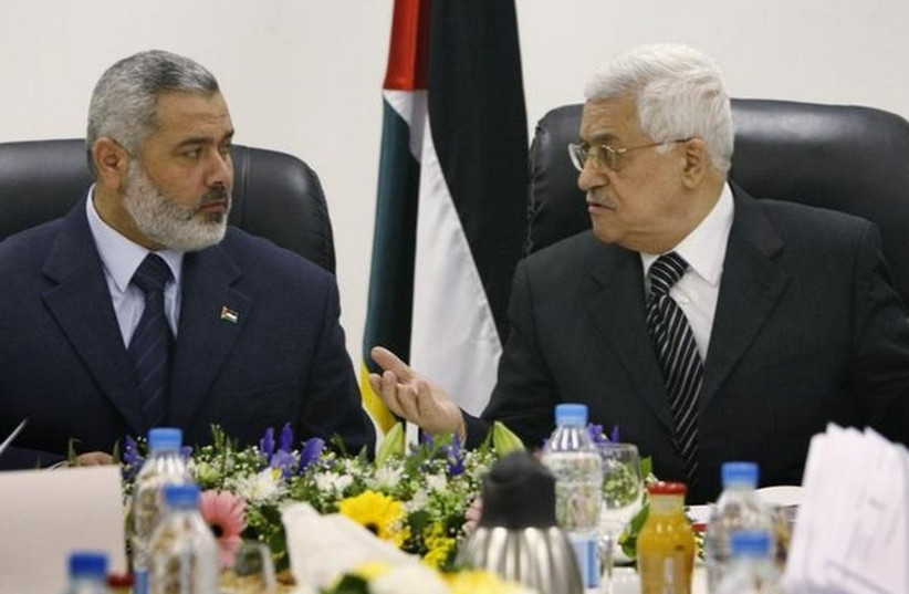 Palestinian Authority President Mahmoud Abbas (R) talks with Hamas leader Ismail Haniyeh. (photo credit: REUTERS)