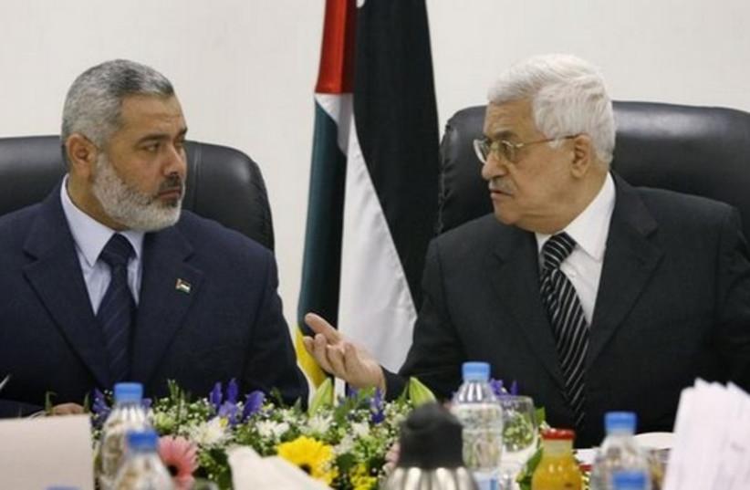 Palestinian Authority President Mahmoud Abbas (R) talks with Hamas leader Ismail Haniyeh. (photo credit: REUTERS)