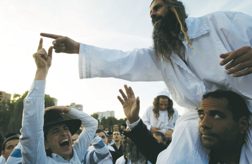 Men gesticulate on the banks of a lake in Uman in September 2010. (photo credit: REUTERS)
