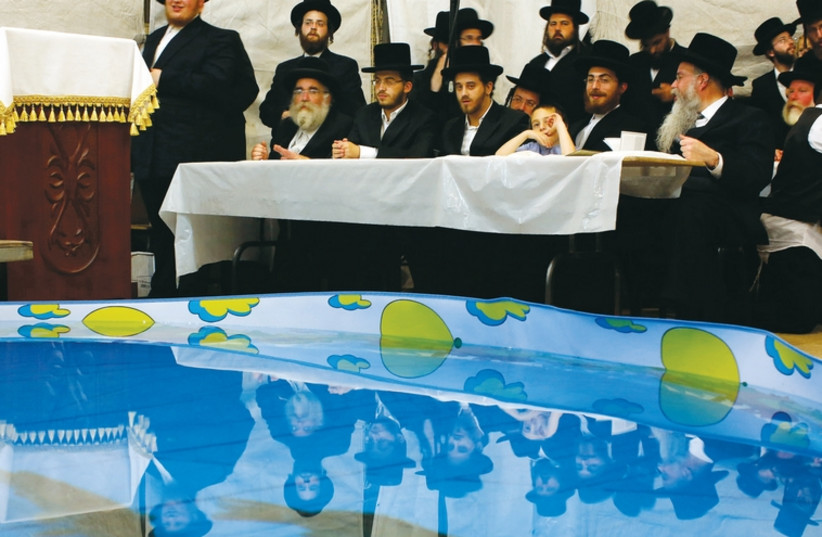 Men pray next to a plastic pool containing fish as they perform the 'Tashlich' ritual in Bnei Brak, in this photo from 2013, ahead of Yom Kippur. (photo credit: REUTERS)