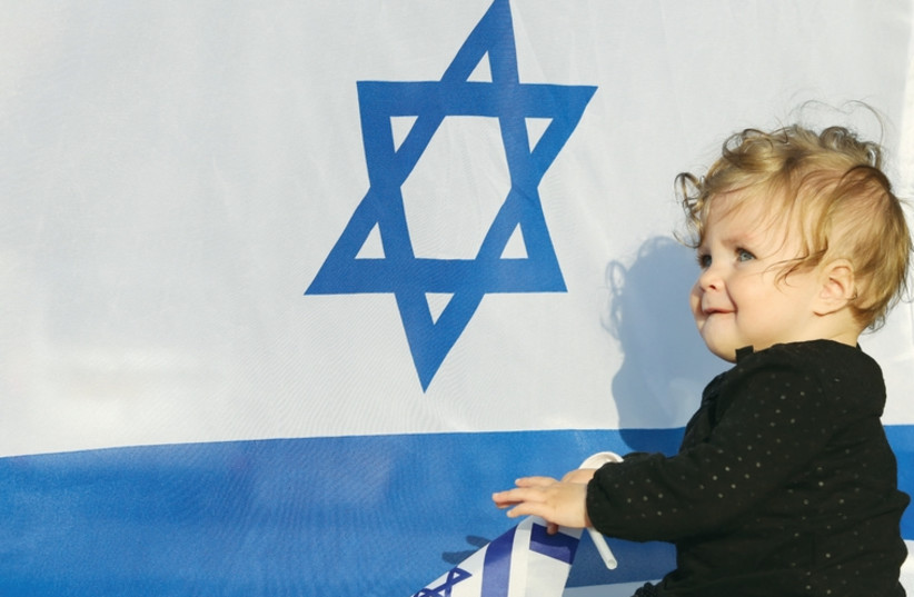 A baby sits in front of an Israeli flag (photo credit: MARC ISRAEL SELLEM/THE JERUSALEM POST)