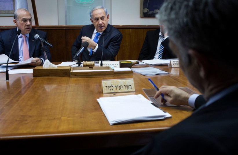 Finance Minister Yair Lapid (R) sits across from Prime Minister Binyamin Netanyahu at the cabinet meeting in Jerusalem. (photo credit: REUTERS)