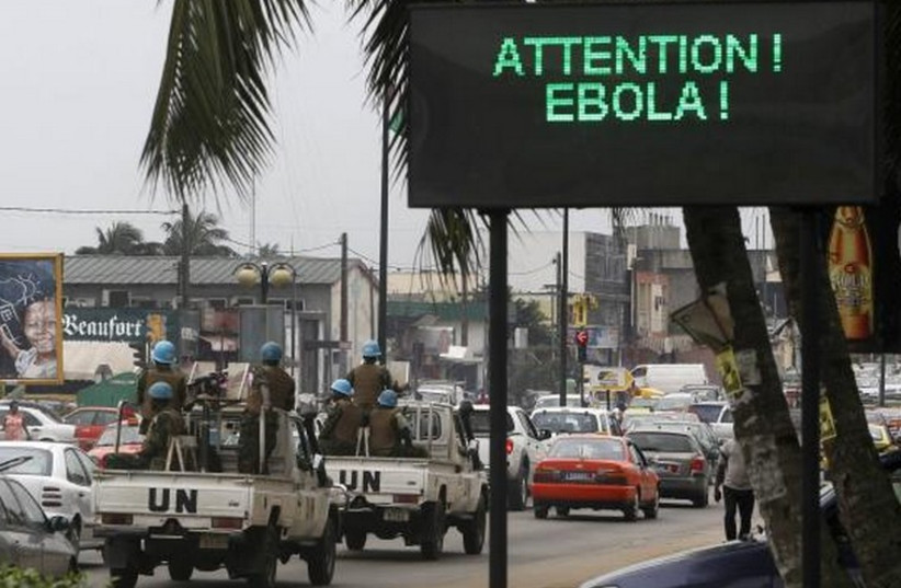 A UN convoy of soldiers passes a screen displaying a message on Ebola on a street in Abidjan. (photo credit: REUTERS)