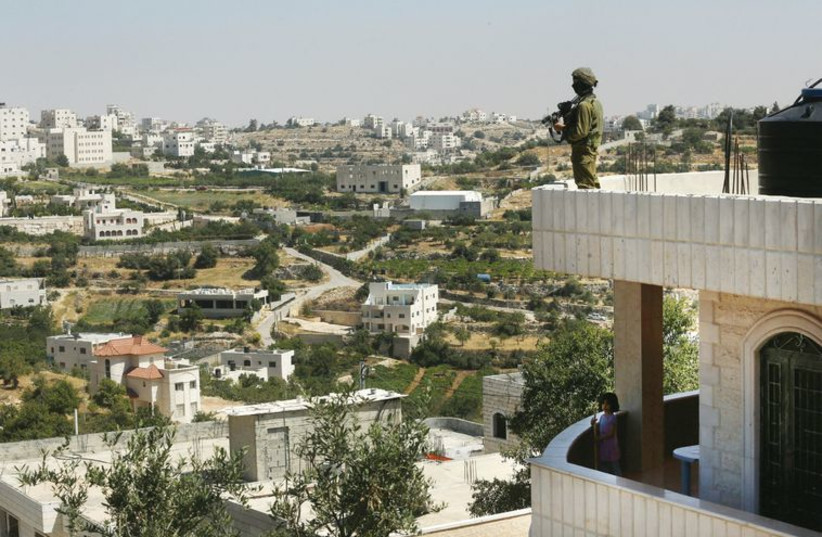 A soldier stands guard on a house in Hebron on June 18, during Operation Brother's Keeper. (photo credit: MARC ISRAEL SELLEM/THE JERUSALEM POST)