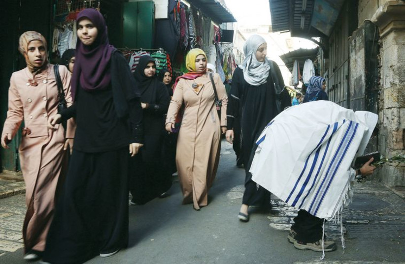 A man prays during Hoshana Raba as Palestinian women walk past. (photo credit: MARC ISRAEL SELLEM/THE JERUSALEM POST)