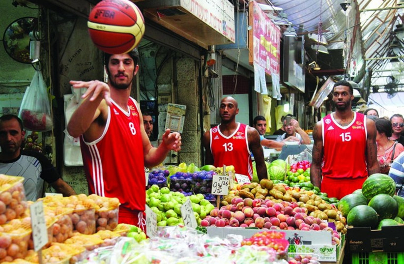 Hapoel Jerusalem basketball players visit the Mahane Yehuda open-air market. (photo credit: OREN BEN HAKON)