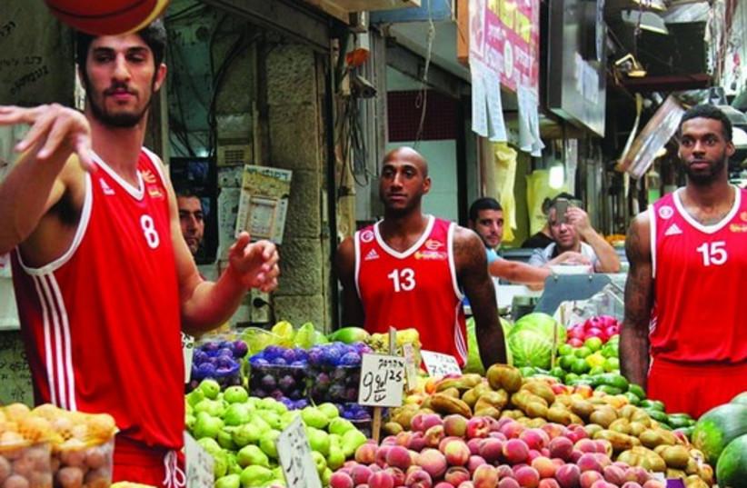 Hapoel Jerusalem basketball players visit the Mahane Yehuda open-air market. (photo credit: OREN BEN HAKON)