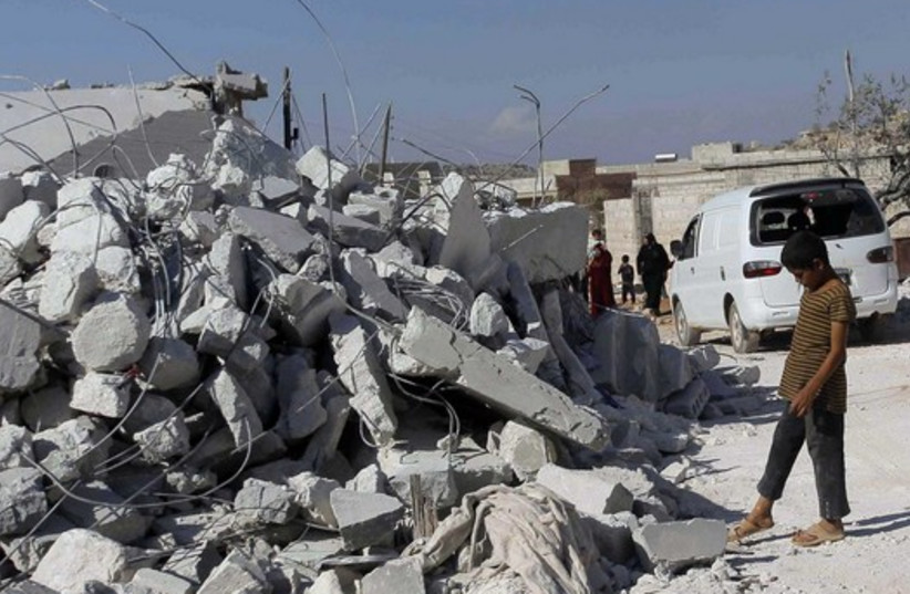 Rubble from US air strike in Syria's Idlib province (photo credit: REUTERS)