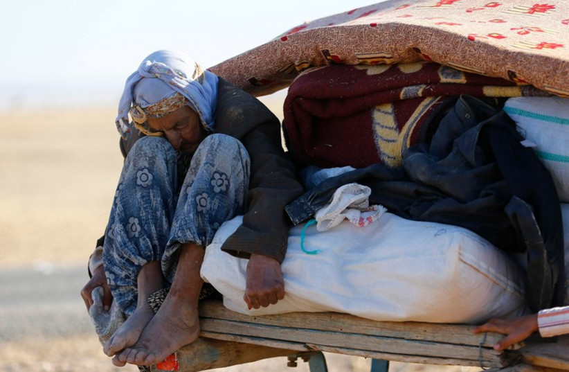 A Kurdish Syrian refugee woman sits on a carriage after crossing the Turkish-Syrian border near the southeastern town of Suruc. (photo credit: REUTERS)