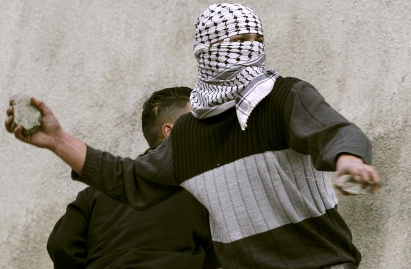 A masked Palestinian teenager throws a stone at Israeli soldiers (photo credit: REUTERS)