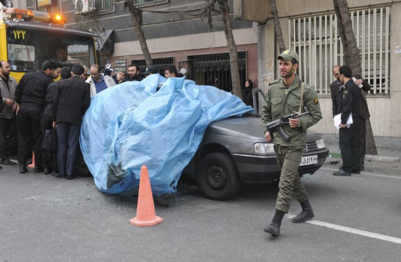 A policeman walks past the car belonging to Iranian nuclear scientist Mostafa Ahmadi-Roshan at a blast site outside a university in northern Tehran January 11, 2012.  (photo credit: REUTERS)