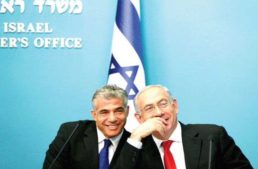 Finance Minister Yair Lapid and Prime Minister Benjamin Netanyahu. (photo credit: RONEN ZVULUN / REUTERS)