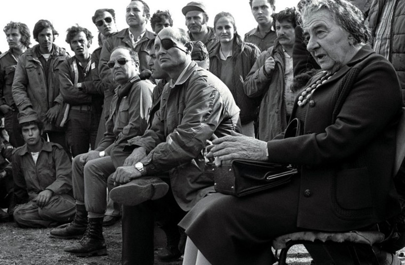 Then-prime minister Golda Meir (R) accompanied by then-defense minister Moshe Dayan, meets with Israeli soldiers at a base on the Golan Heights after intense fighting during the 1973 Yom Kippur War. (photo credit: REUTERS)