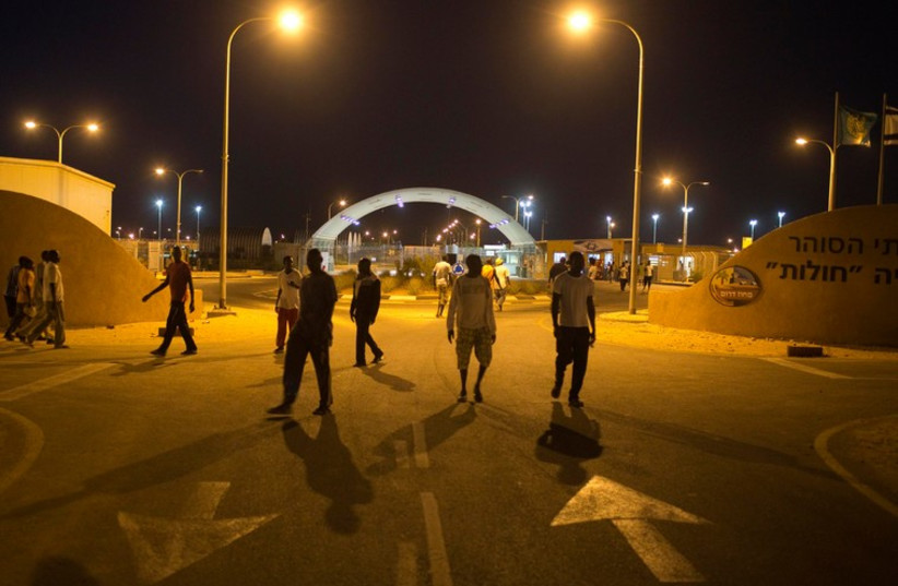 African migrants walk in front of the entrance to Holot open detention center in the Negev  (photo credit: REUTERS)