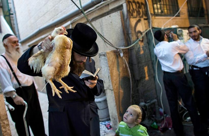A man performs the ancient Jewish ritual of kaparot (photo credit: REUTERS)