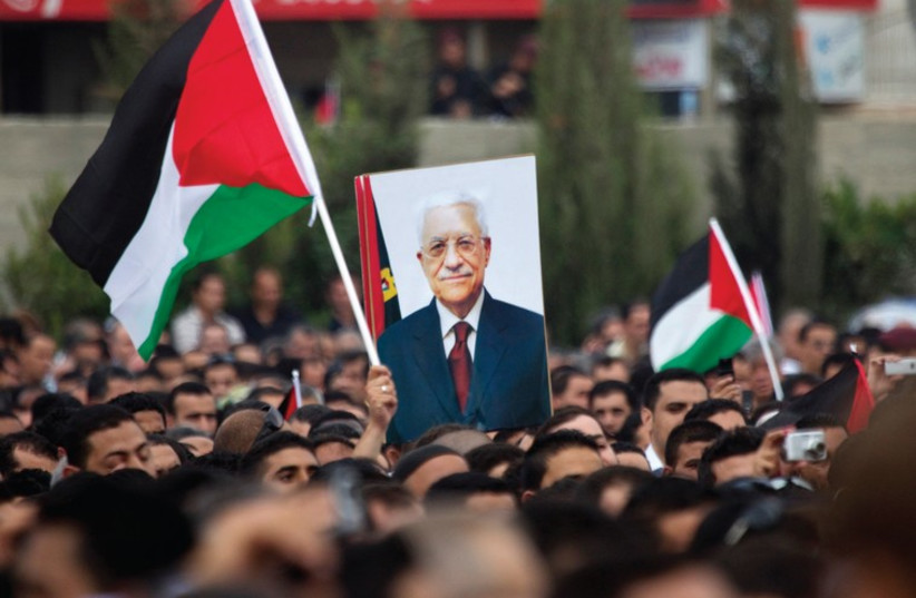Palestinians marching with a poster of Mahmoud Abbas in Ramallah. (photo credit: REUTERS)