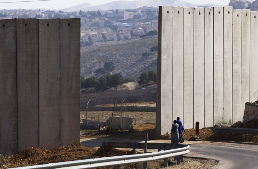 Palestinians walk near an opening in Israel's controversial barrier in the east Jerusalem neighbourhood of A-tur (photo credit: REUTERS)
