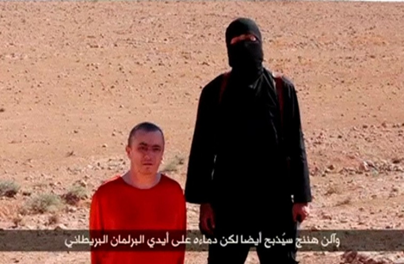 A masked man stands next to a kneeling man identified as British citizen Alan Henning (L) in this still image taken from video released by Islamic State (photo credit: REUTERS)