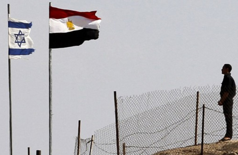 An Egyptian soldier stands near the Egyptian national flag and the Israeli flag at the Taba crossing between Egypt and Israel (photo credit: REUTERS)