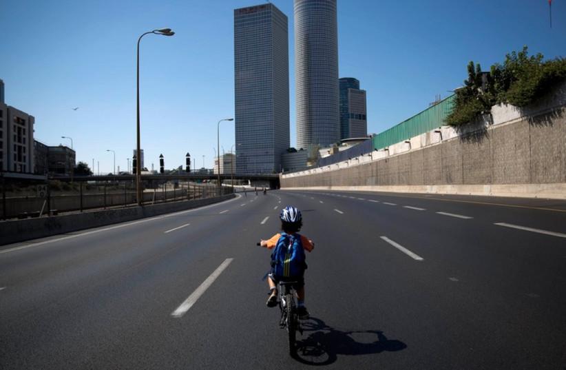 An Israeli boy rides his bike on an empty motorway during Yom Kippur in Tel Aviv (photo credit: REUTERS)