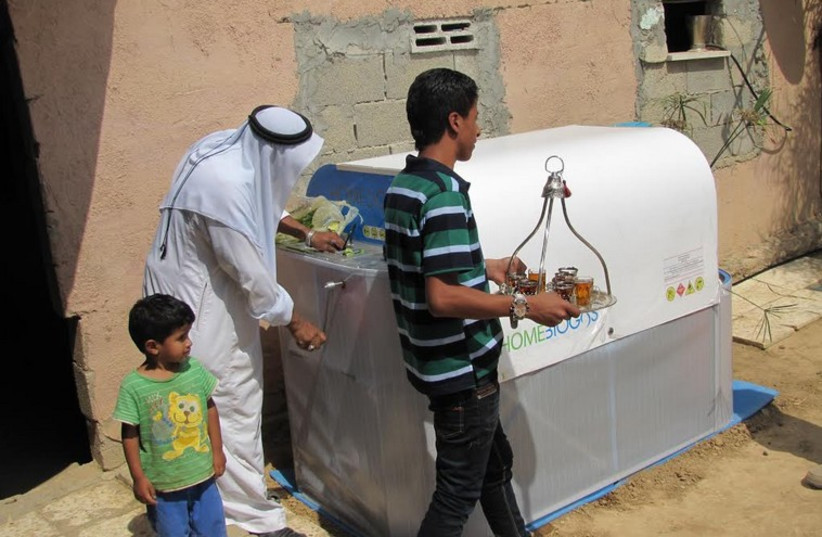 A beduin Umm Batin resident uses the HomeBioGas system. (photo credit: MINISTRY OF ENVIRONMENTAL PROTECTION)