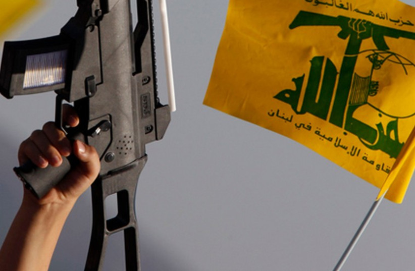Lebanese child holds up plastic toy during pro-Hezbollah rally (photo credit: REUTERS)