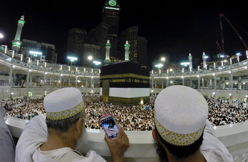 Muslim pilgrims take pictures for the pilgrims as they pray around the holy Kaaba at the Grand Mosque, during the annual hajj pilgrimage in Mecca (photo credit: REUTERS)