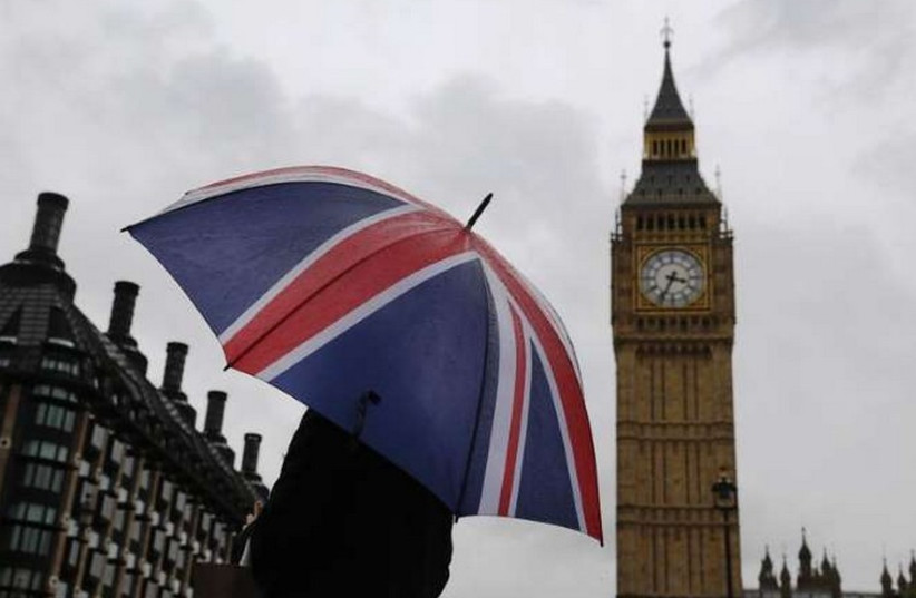 A woman holds a Union flag umbrella in front of the Big Ben clock tower (R) and the Houses of Parliament in London (photo credit: REUTERS)