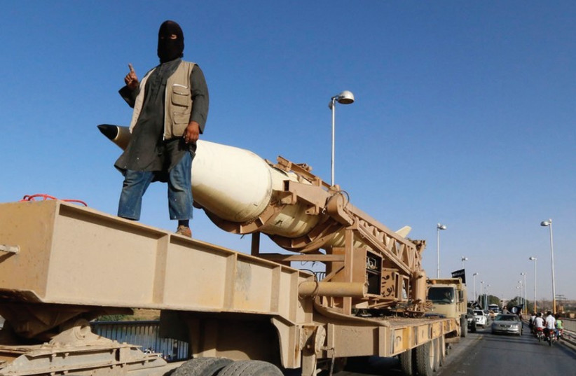 AN ISIS member rides on a rocket launcher in Raqqa in Syria two months ago (photo credit: REUTERS)