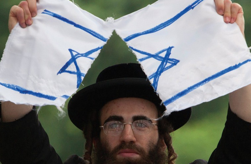 A MAN rips a cloth depicting an Israeli flag during a protest against Israel (photo credit: REUTERS)