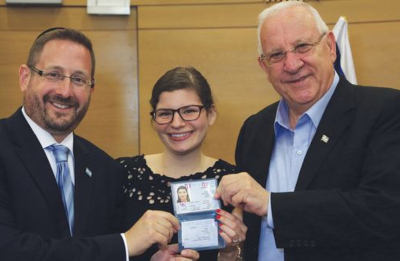 Dov Lipman and President Reuven Rivlin present a ID card to a new immigrant to Israel in July (photo credit: SASSON TIRAM)
