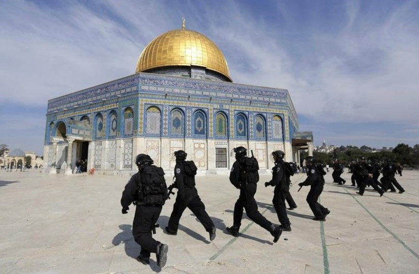 Police officers run in front of the Dome of the Rock during clashes with stone-throwing Palestinians. [File] (photo credit: REUTERS)
