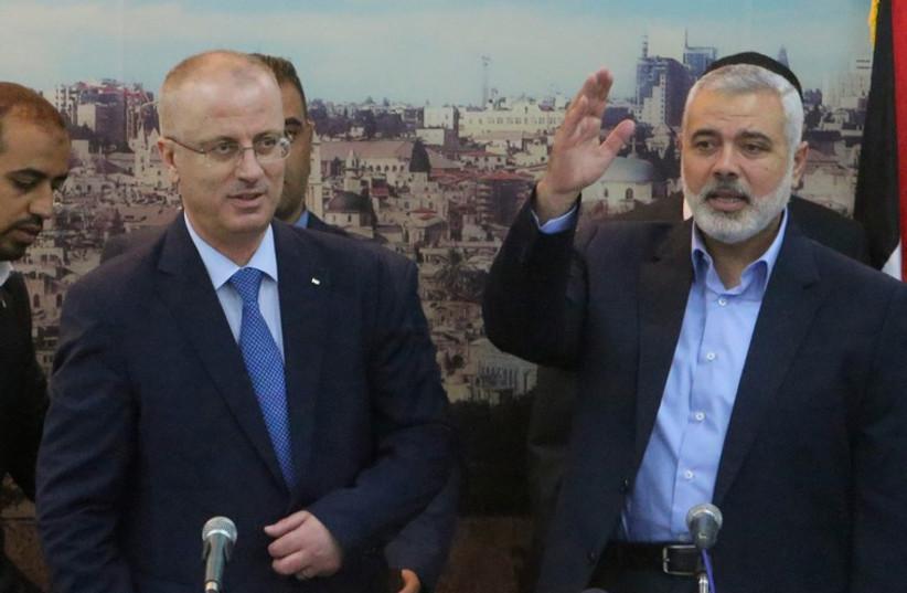 Senior Hamas leader Ismail Haniyeh (R) waves as he hosts PA Prime Minister Rami Hamdallah at his house in Gaza City October 9, 2014. (photo credit: REUTERS)