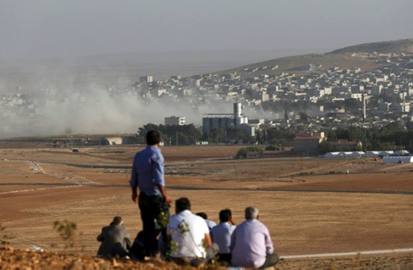 Turkish Kurds look towards the Syrian Kurdish town of Kobani from the top of a hill close to the border line between Turkey and Syria near Mursitpinar bordergate (photo credit: REUTERS)