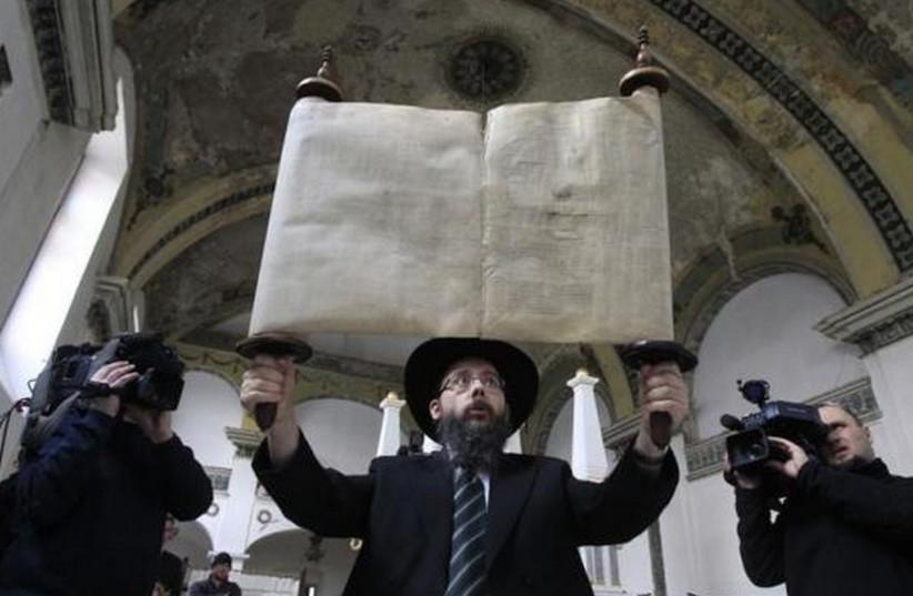 Rabbi Baruch Oberlander holds up a Torah scroll (photo credit: REUTERS)