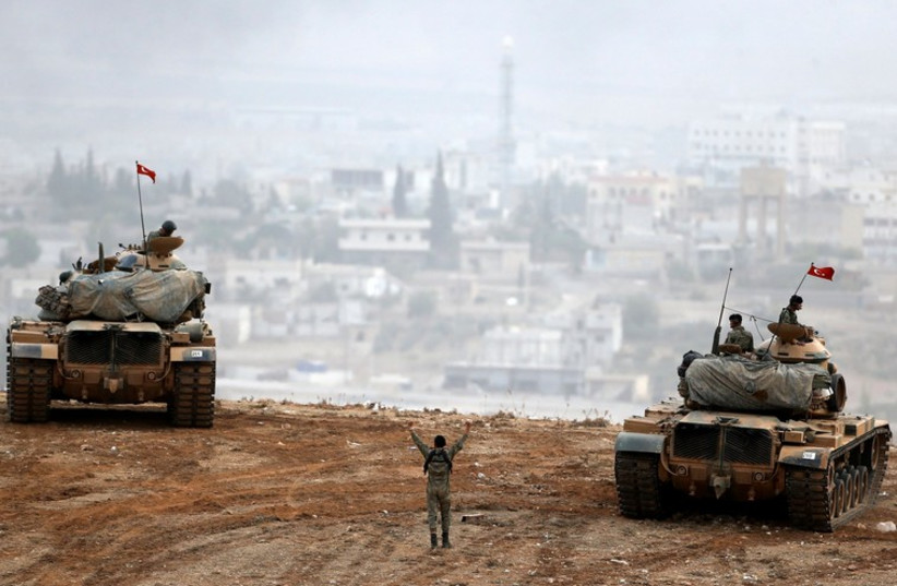 Turkish army tanks manoeuver as Turkish Kurds watch over the Syrian town of Kobani (photo credit: REUTERS)