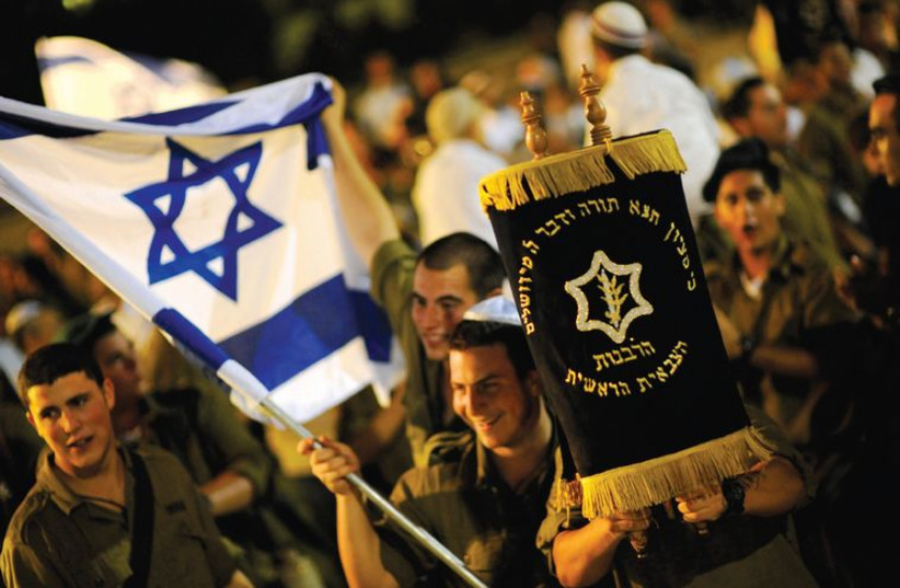 Soldiers dance with Torah scrolls during the celebrations of Simhat Torah in the Eshkol region in the Negev in September 2010. (photo credit: AMIR COHEN - REUTERS)