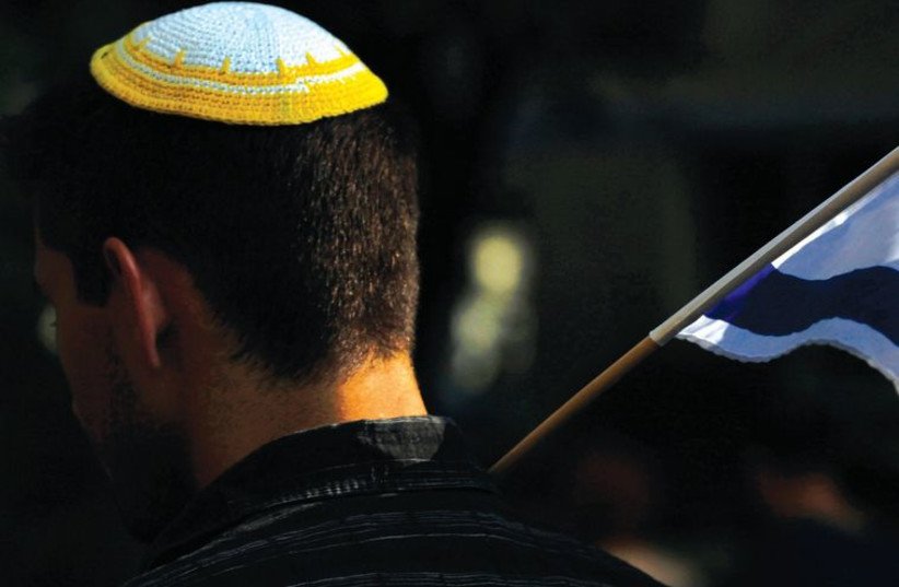 A man holds Israel's flag during the March of Remembrance commemorating the 71st anniversary of the beginning of the liquidation of the Warsaw Ghetto in Warsaw last year. (photo credit: KACPER PEMPEL/REUTERS)