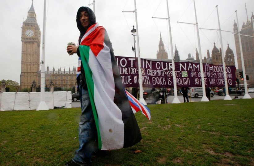 A pro-Palestinian supporter wears a Palestinian and Union flag outside the Houses of Parliament in London.  (photo credit: REUTERS)
