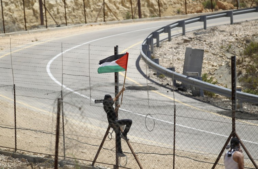 A protester places a Palestinian flag at the Israeli barrier fence in the West Bank village of Rafat near Ramallah (photo credit: REUTERS)