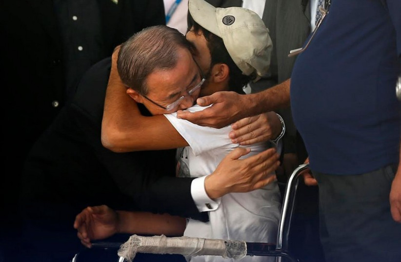 United Nations Secretary-General Ban Ki-moon (L) hugs wheelchair-bound Palestinian Mohammed Abed al-Dayem at a UN-run school in the northern Gaza Strip (photo credit: REUTERS)