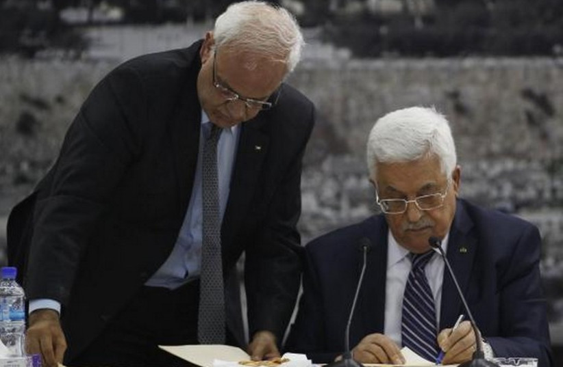 Palestinian Authority President Mahmoud Abbas (R) and his chief peace negotiator, Saeb Erekat, in Ramallah (photo credit: REUTERS)