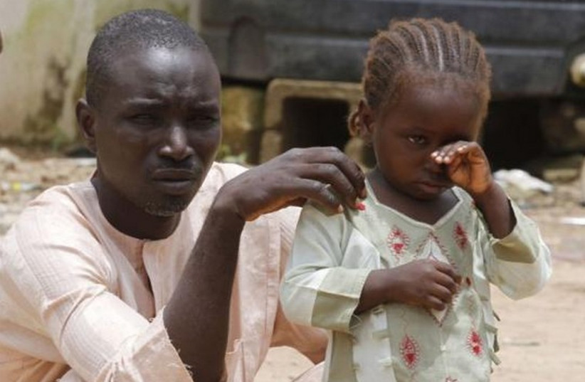 A girl rubs her eye beside her father in an internally displaced persons (IDP) camp, that was set up for Nigerians fleeing the violence committed against them by Boko Haram militants (photo credit: REUTERS)
