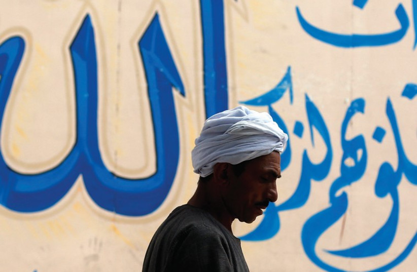 A MAN walks past a graffiti of verses from the Koran at downtown in Cairo (photo credit: REUTERS)