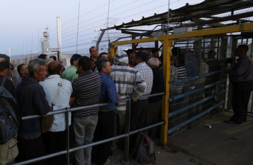 Palestinians wait to cross into Israel at Jalama crossing near Jenin  (photo credit: REUTERS)