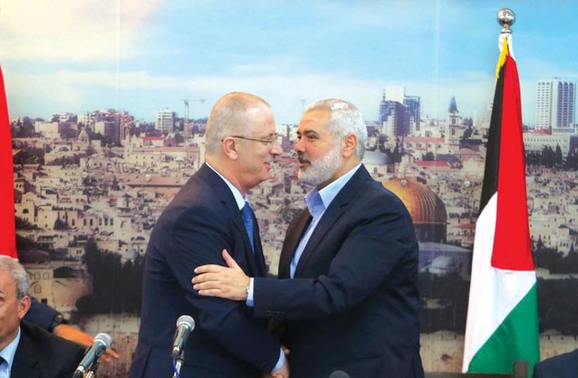 Hamas leader Ismail Haniyeh (right) welcomes Palestinian Authority Prime Minister Rami Hamdallah to the Gaza Strip, October 9. (photo credit: IBRAHEEM ABU MUSTAFA / REUTERS)