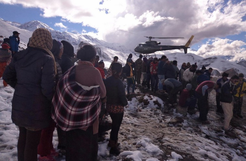 People gather near a helicopter belonging to Nepal Army used to rescue avalanche victims at Thorang-La in Annapurna Region (photo credit: REUTERS)