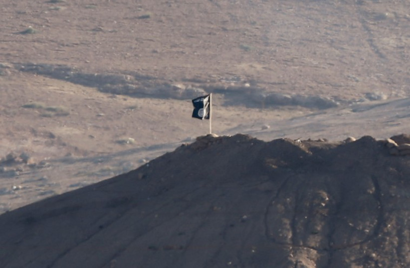 A black flag belonging to the Islamic State is seen near the Syrian town of Kobani, as pictured from the Turkish-Syrian border (photo credit: REUTERS)