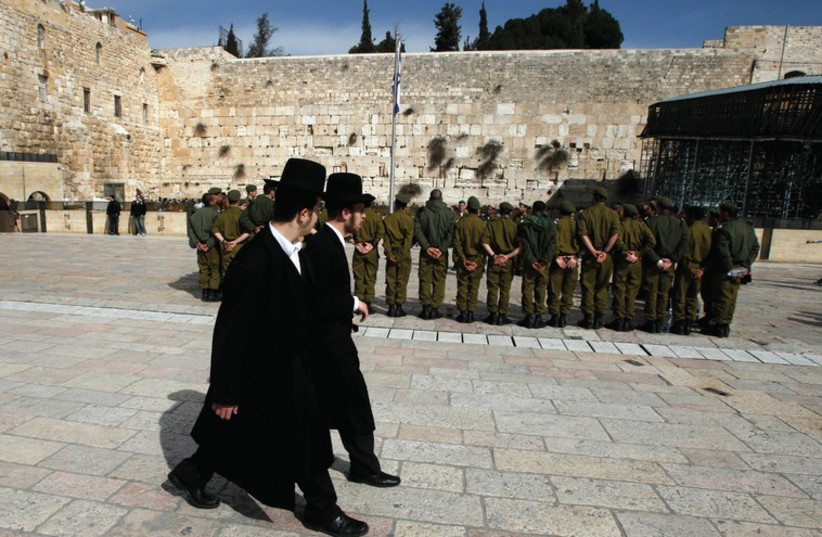 ULTRA-ORTHODOX MEN walk past soldiers at the Kotel in Jerusalem (photo credit: REUTERS)